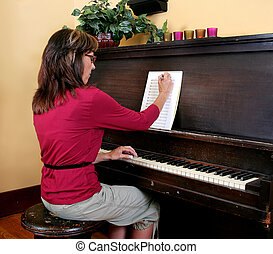 woman composing piano music - a woman in red writing new...