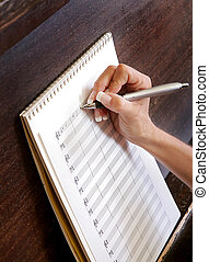 composing new music - close up of a womans hand writing...