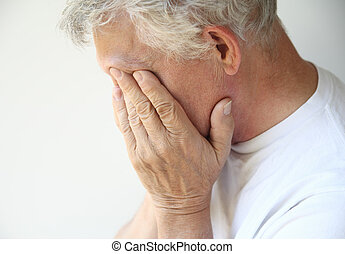 older man overcome with depression - senior man covers his...