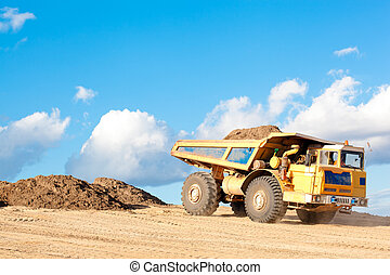 Heavy dump truck unloads soil on the sand at a construction...