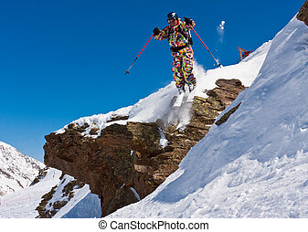 Skier jumping from a cliff Illuminated by a bright sun in...