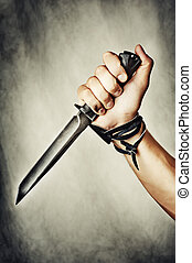 Knife in hand - male hand holding combat black Knife