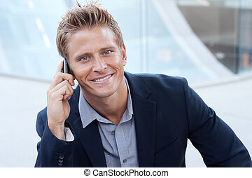 Closeup portrait of handsome business man using cell phone,...
