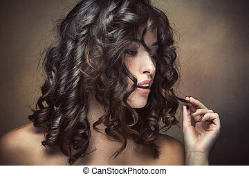 haircare - sensual brunette woman with shiny curly silky...