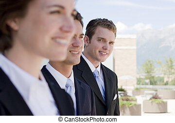 Business team - small group of business people standing with...