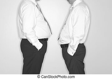 office politics - front view of two businessmen standing...