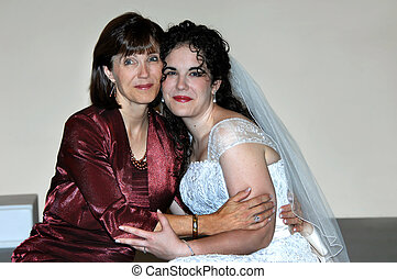 Cheek to Cheek - Bride and mother cling to each other before...