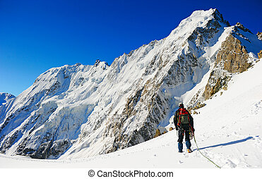 Climber reaching the summit of mountain - Mountaineer sport...