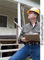 Estimating and Inspecting - A man in a hard hat standing in...
