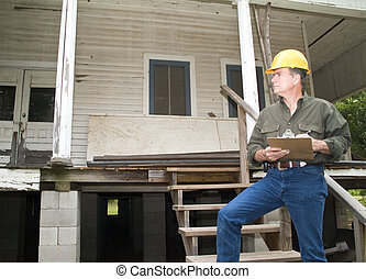Inspecting the Damage - A man in a hard hat, holding a...