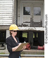 Estimating the cost - A woman in a hard hat in front of an...