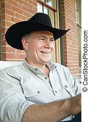 Happy Cowboy 1 - A man sitting on a porch wearing a cowboy...