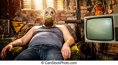 man in a gas mask - person in a gas mask sits on an armchair