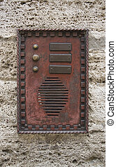 historic doorbell plate on rough facade, seen in Italy