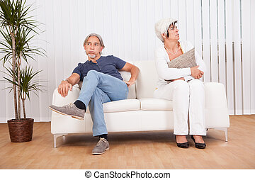 Senior couple after an argument sitting at opposite ends of...