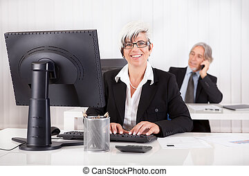 Smiling secretary or personal assistant sitting working at...