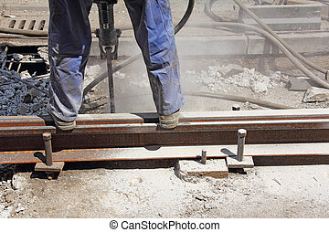 Worker with pneumatic hammer drill equipment breaking...