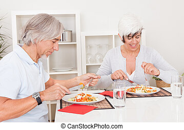 Senior couple eating a meal - Attractive senior couple...