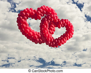 Two heart-shaped baloons in the sky, the symbols of love