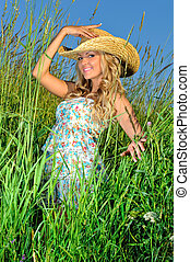 Beautiful blonde woman in straw hat on the nature.