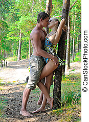 Beautiful man and woman holding and kissing on the nature.