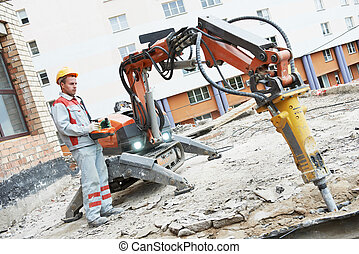 builder worker operating demolition machine
