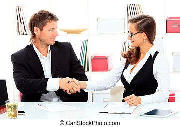 consensus - Business woman and businessman shaking hands at...