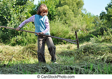 child working with a rake - elementary age child working...