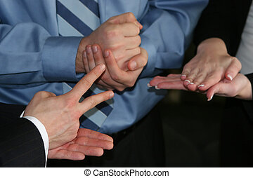 hand gestures - close-up on three businesspeople's hands...