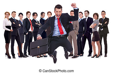 young leader jumping for joy in front of his team - business...