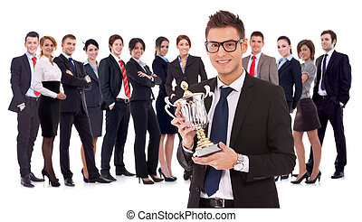 businss man holding a trophy in fron of his team - winning...
