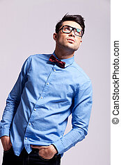 fashion man wearing bow tie and glasses looks up - young...
