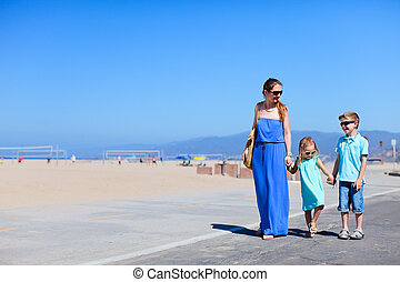 Family at Santa Monica beach - Mother and two kids walking...