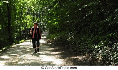 grandma is wandering on a forest track