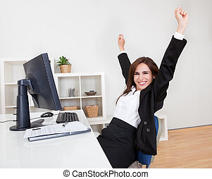 Businesswoman Cheering At Desk - Portrait of Cheering...