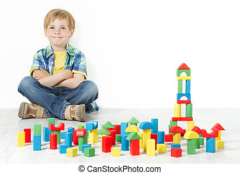 Boy and construction blocks toys - Boy sitting next to...