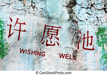 Wishing well sign written on stone wall