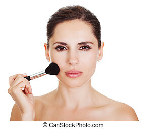 Beautiful woman applying blusher to her cheekbones with a...