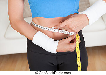 Happy woman measuring her waist with a tape measure to see...