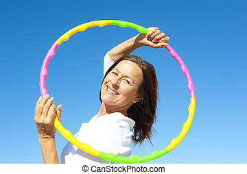 Active senior woman hula hoop exercise - Portrait of happy...