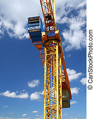 yellow crane against sky with cumulus clouds