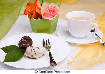 sweet cake on dish with rose and coffee