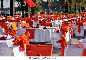 banquet - long lines of festively decorated tables and with...