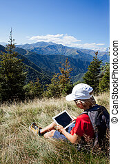 Boy sitting in a mountain meadow using a tablet computer -...