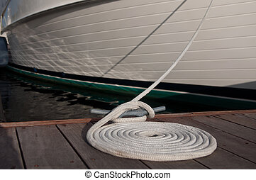 Docked Boat - Dock cleat with a white line tied around it,...