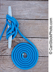 Coiled Line - Blue rope coiled on a wooden dock and tied to...