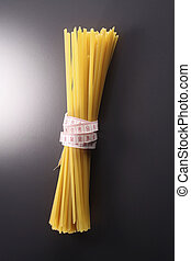 health eating - Sheaf of spaghetti tied with a tape measure
