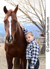 Boy and Horse - Young boy in blue leaning against his horse
