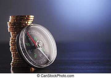 finance idea - Stack of coins next to Compass