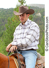 Young cowboy - Attractive young cowboy on horseback in the...